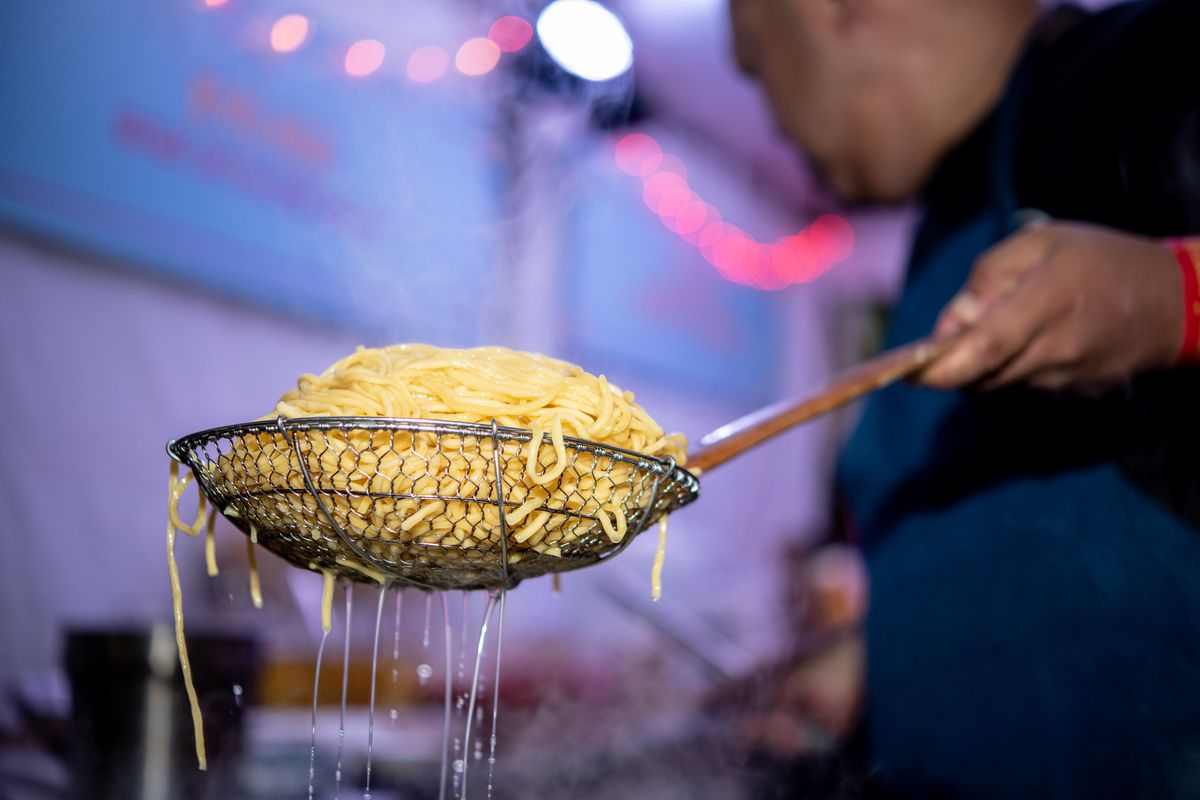 A man holds a strainer full of squiggly noodles at an outdoor stall. It's twilight, and string lights illuminate the outdoor kitchen.