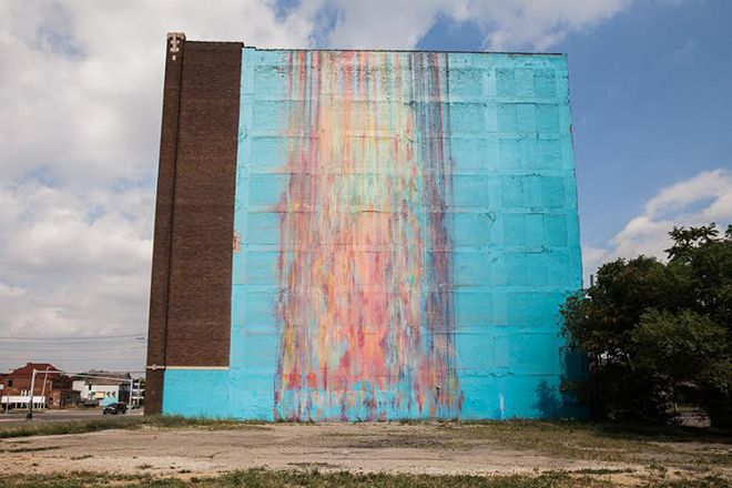 A large building with a blue wall with a mural painted on it.