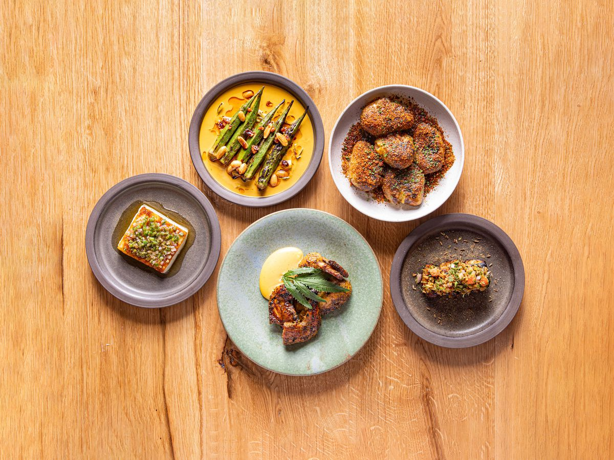 A selection of dishes from Chet Sharma's BiBi, on colourful stone-esque plates, on a wooden backdrop.