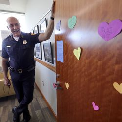 """Salt Lake Police Chief Mike Brown shows off a note about the recent loss of his father as well as a """"heart attack"""" of heart notes left by Civilian Explorers on his office door in Salt Lake City on Wednesday, July 15, 2020."""