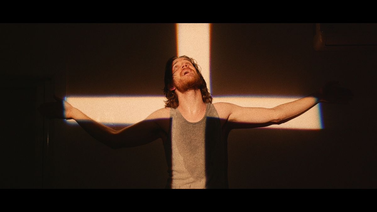 Bo Burnham poses with a crucifix projected on him in Bo Burnham's Inside