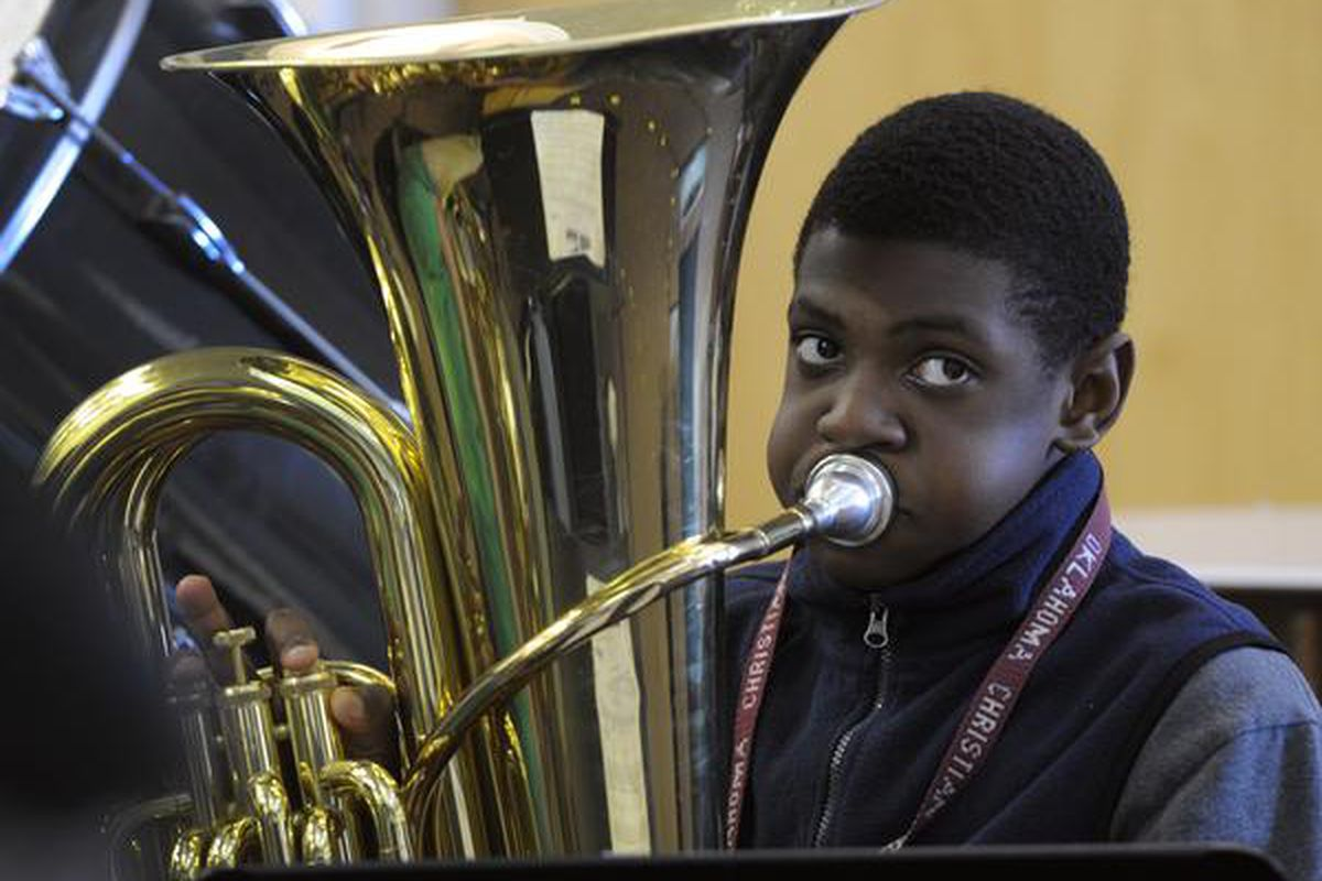 Adrian Jackson, 12, practices his tuba with members of the 6th-grade concert band at Noel Community Arts School in 2012.