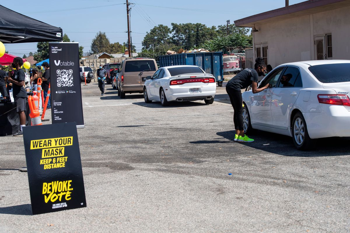 """A sign reads """"Wear your mask, keep 6 feet distance, BeWoke Vote"""" beside a line of cars at a drive-through voter registration event."""