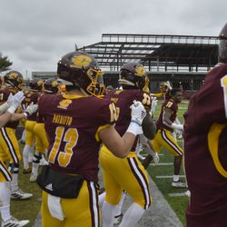 The CMU football team runs onto the field after the clock strikes zero to celebrate.