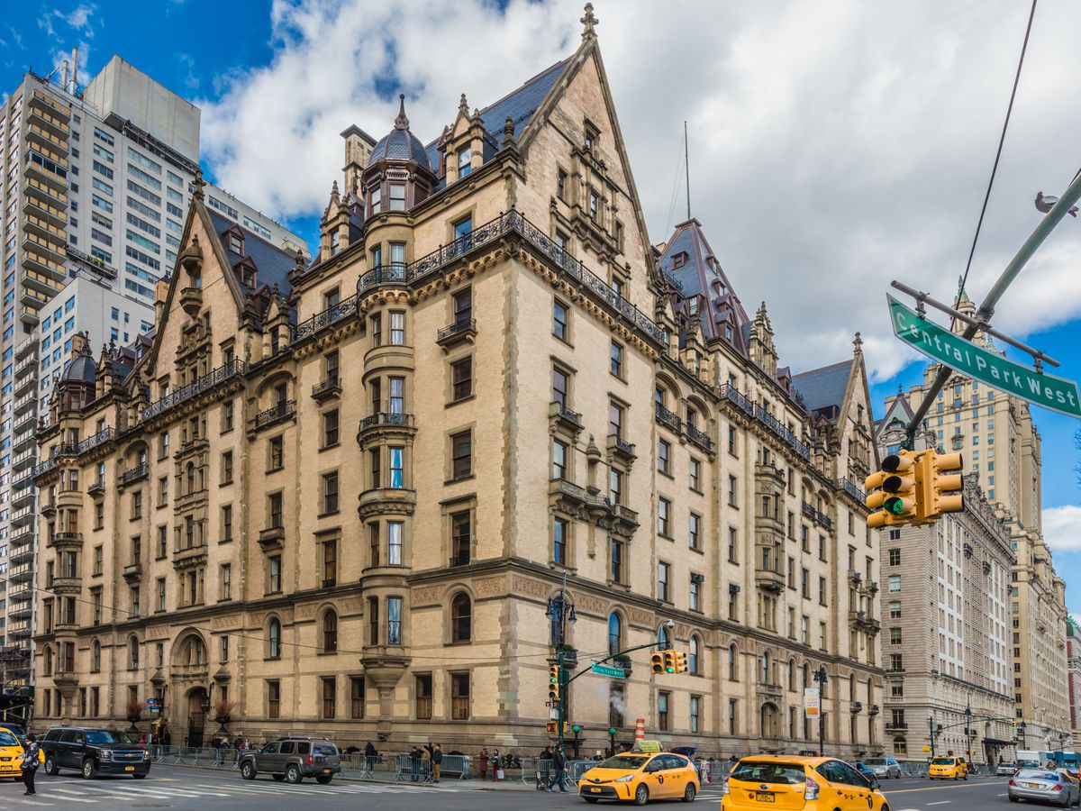 The exterior of the Dakota in New York City. The building is tall and ornately designed with multiple windows and turrets. There is an intersection in front with cars, yellow taxi cabs, and pedestrians.