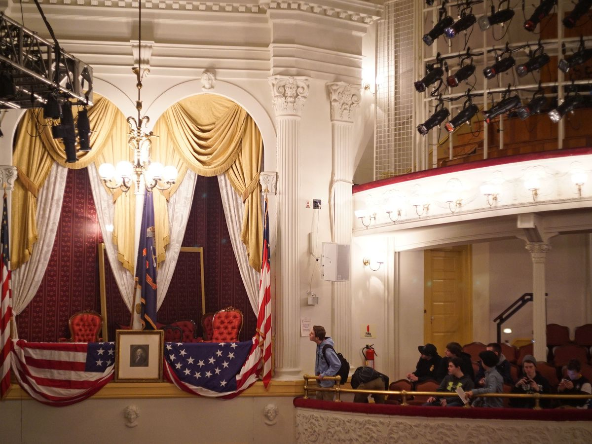 An old theater house where box seating is framed by curtains and American flags.