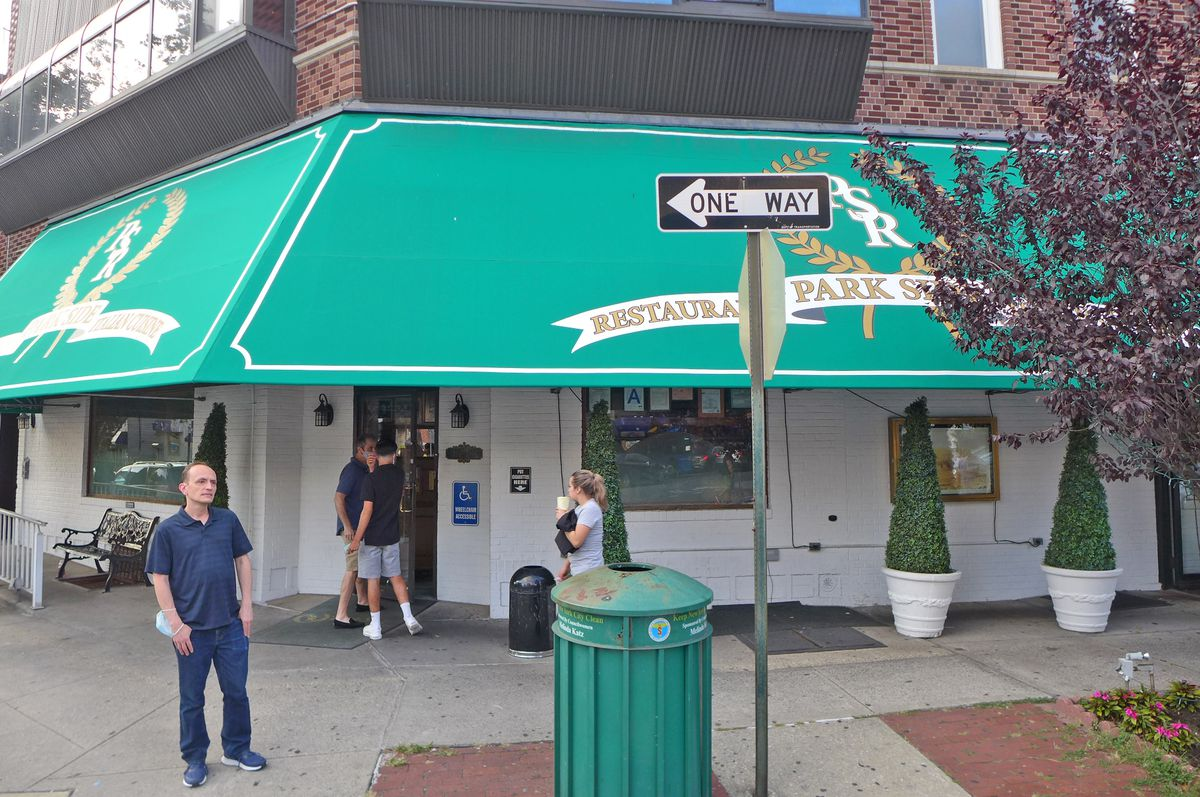 A man stands in front of the corner entrance to a restaurant.