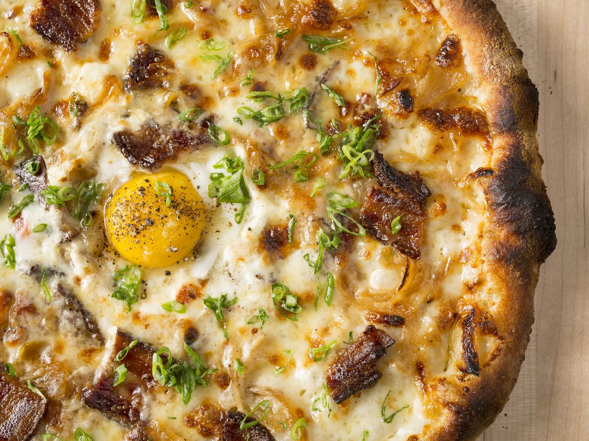 A thin-crust pie with charred crust, egg, cream sauce and pancetta.