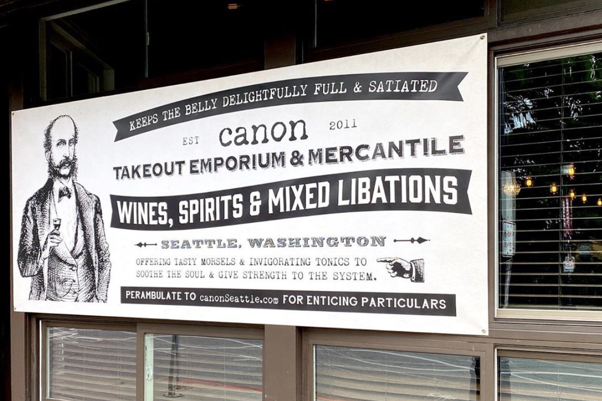 """The old fashioned sign outside Canon on Capitol Hill, which says, """"Canon: Takeout Emporium & Mercantile, Wines, Spirits, Mixed Drinks, and Libations"""""""