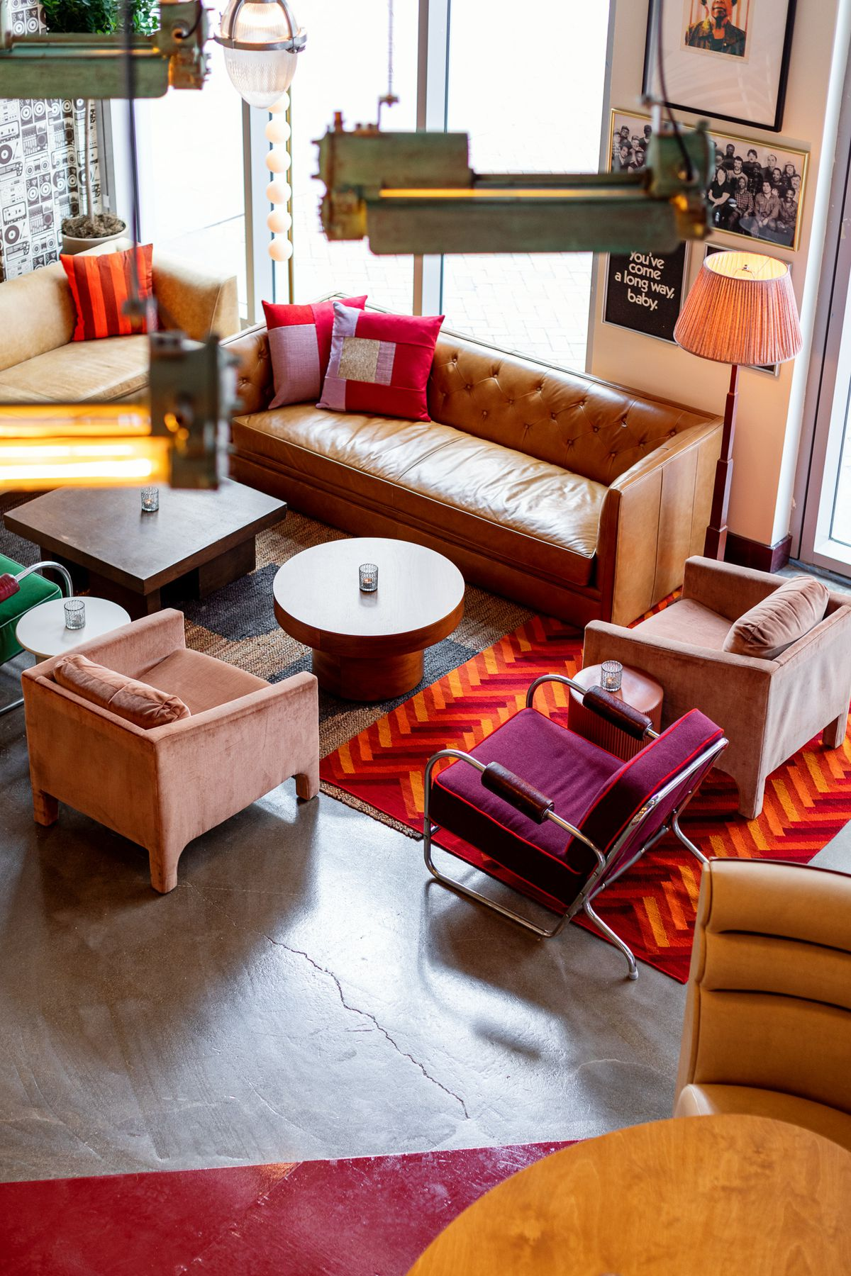 An aerial view from the mezzanine of two sofas, and a few eclectic chairs surrounding two wooden coffee tables on the first floor