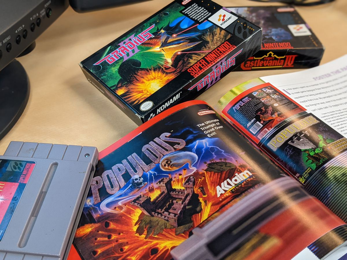 A book about Super NES games is opened to the Populous page.