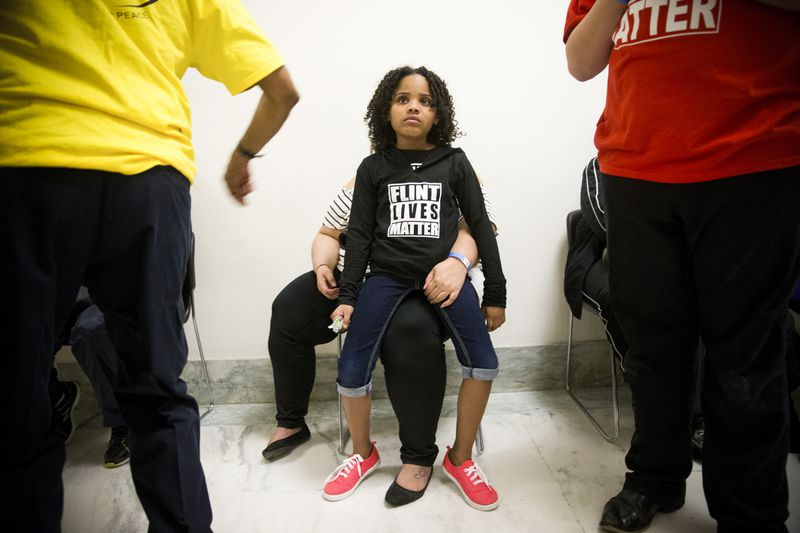 Mari Copeny, 8, sits on her mother's lap.