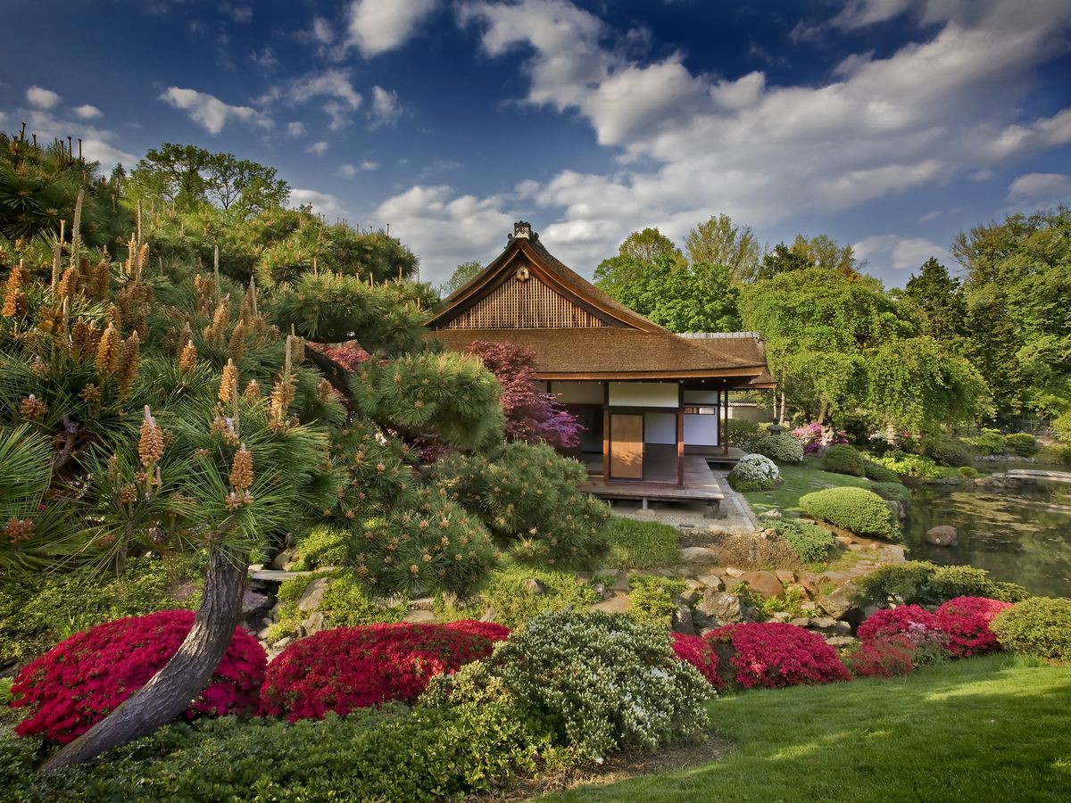 The exterior of the Shofuso Japanese House and Garden. The house is surrounded by colorful flowers, shrubs, trees, and grass.