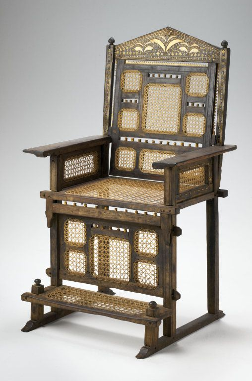 A wooden chair with a built in foot rest.