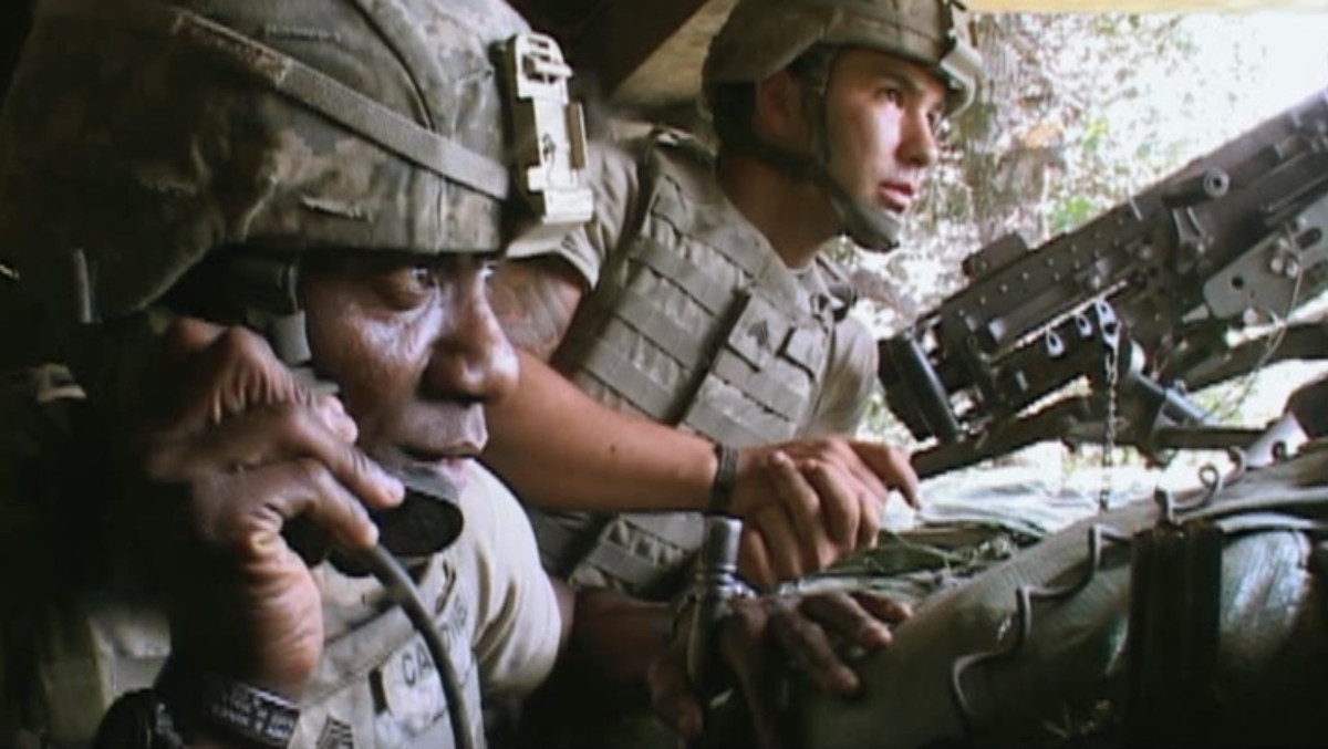 Two soldiers sit in a trench, one on the phone and one on a machine gun, in Restrepo