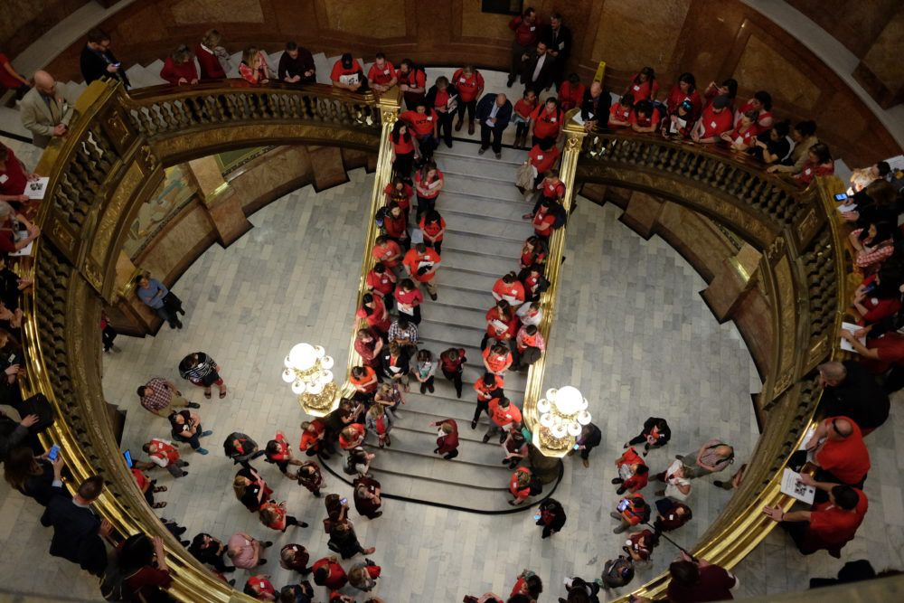 Teachers in red gather in the rotunda of the Colorado State Capitol in 2018. They line the stairway and are seen from above.