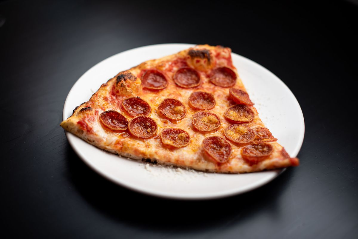 A triangle pepperoni slice on a black table and white plate.