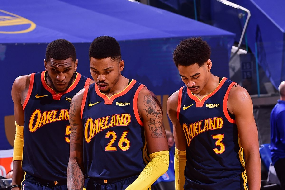 Kent Bazemore #26 talks with Kevon Looney #5 and Jordan Poole #3 of the Golden State Warriors against the Philadelphia 76ers on March 23, 2021 at Chase Center in San Francisco, California.