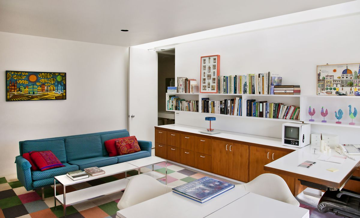 A bright home office with a row of wood cabinets along the back wall under wall-mounted shelving for books and framed folk art collections. A turquoise midcentury sofa is placed at left, sitting on a checkered carpet.
