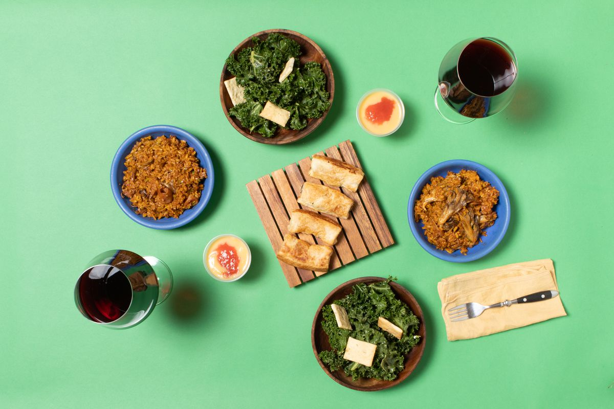 Top-down view of bowls of paella, glasses of red wine, and kale salad against a green background