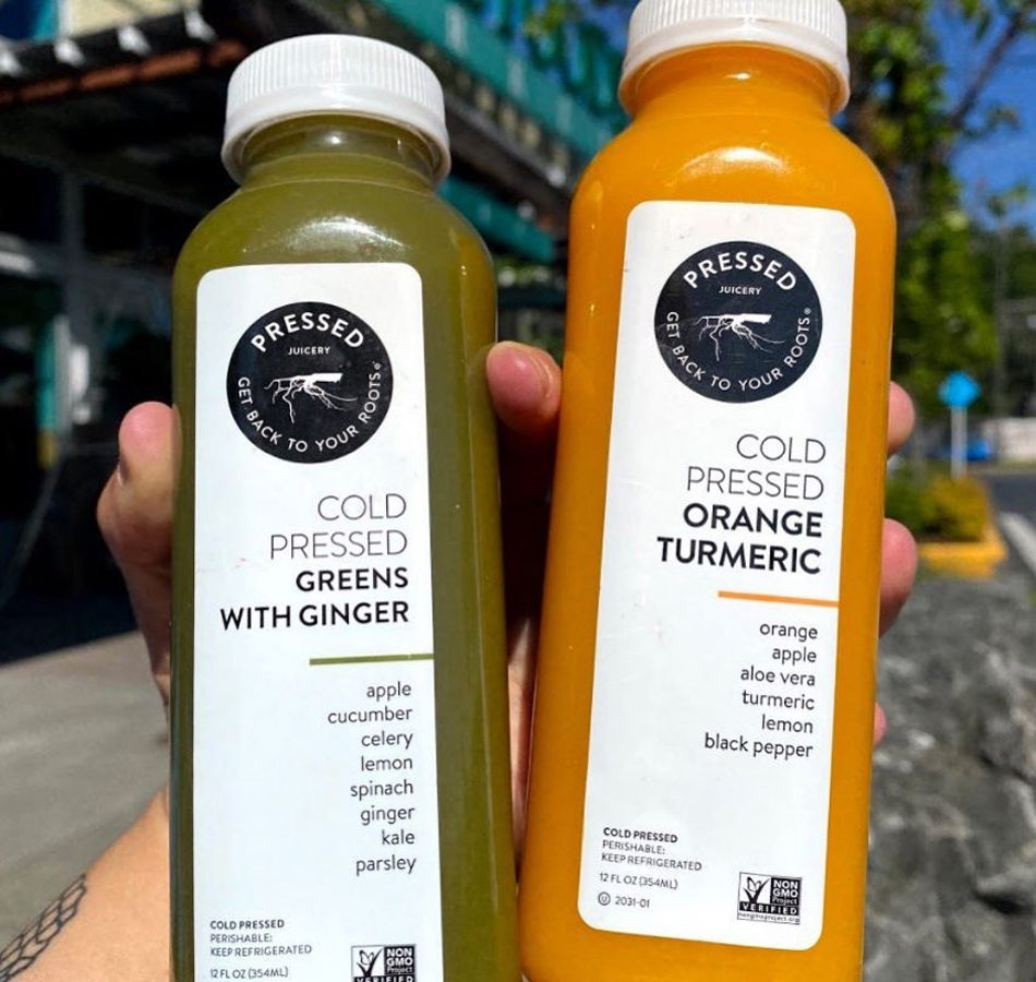Two of teh 40 different cold-pressed juice options served daily at Pressed Juicery.