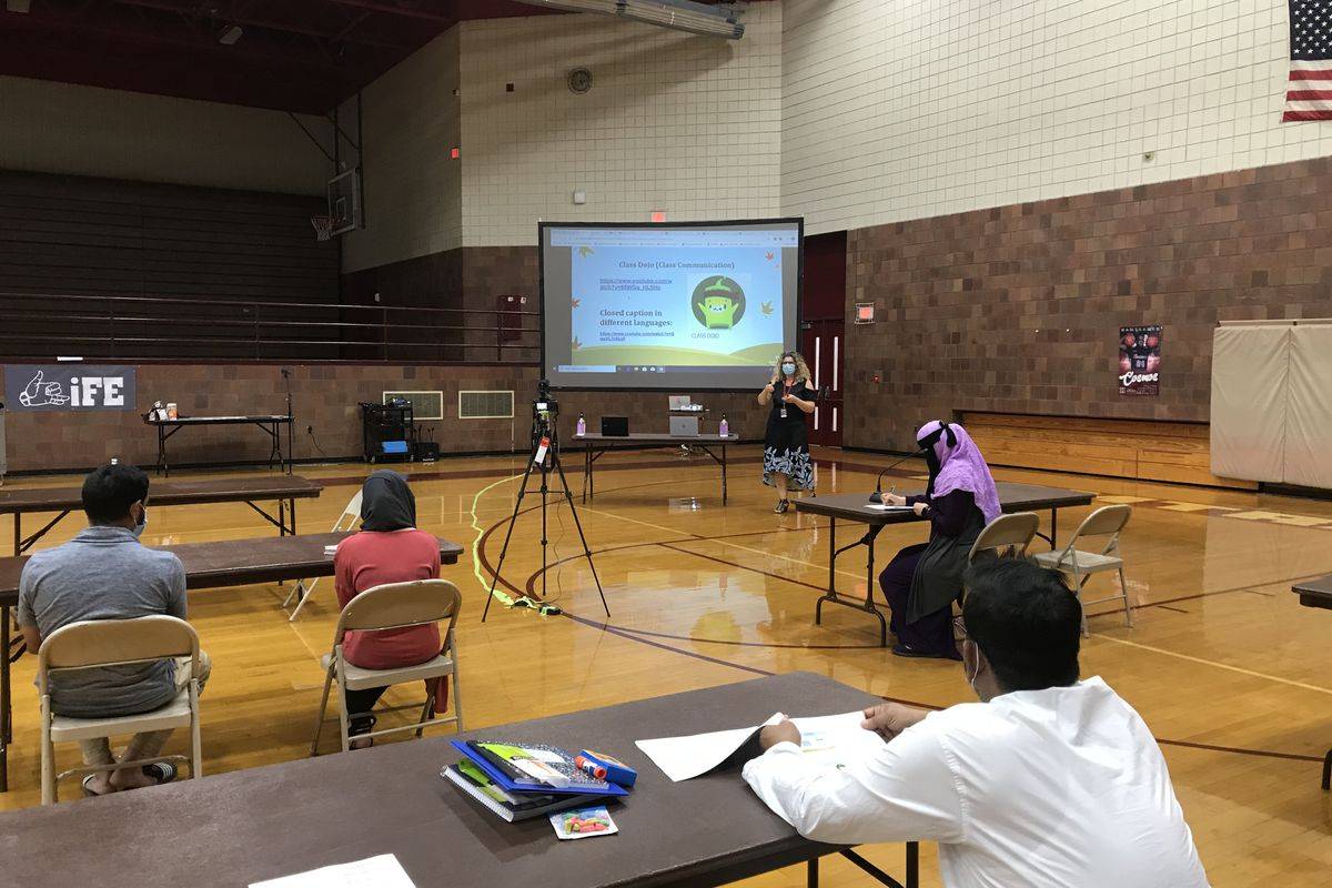 English learners and their parents sit at a social distance in a Hamtramck gym during the coronavirus pandemic to learn about online instruction.