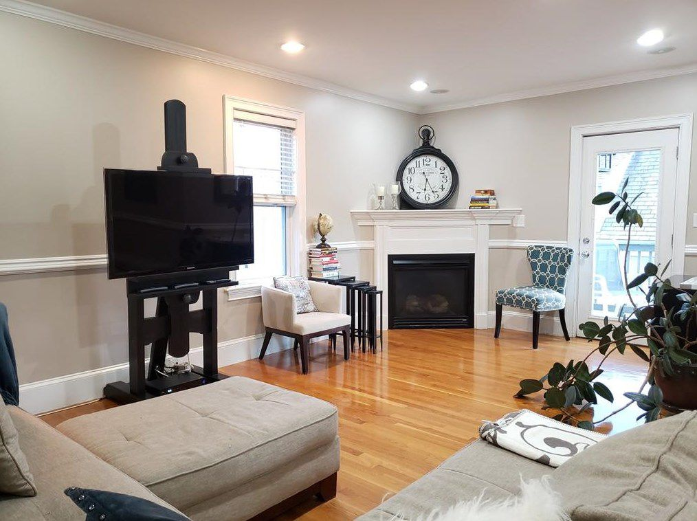 An open living room with an easel holding up a TV, and there's a fireplace in the corner.