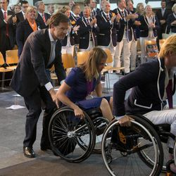 Prime Minister Mark Rutte, left, pushes London 2012 Paralympic silver medallist wheelchair racer Amy Siemons up the ramp during a celebration honouring medal-winning Dutch Paralympic athletes on the eve of parliamentary elections in The Hague, Netherlands, Tuesday Sept. 11, 2012. According to a summary of recent polls compiled by national broadcaster NOS Tuesday, Rutte's free-market VVD party is running neck-and-neck with the center-left Labor Party PvdA of Diedrik Samsom.