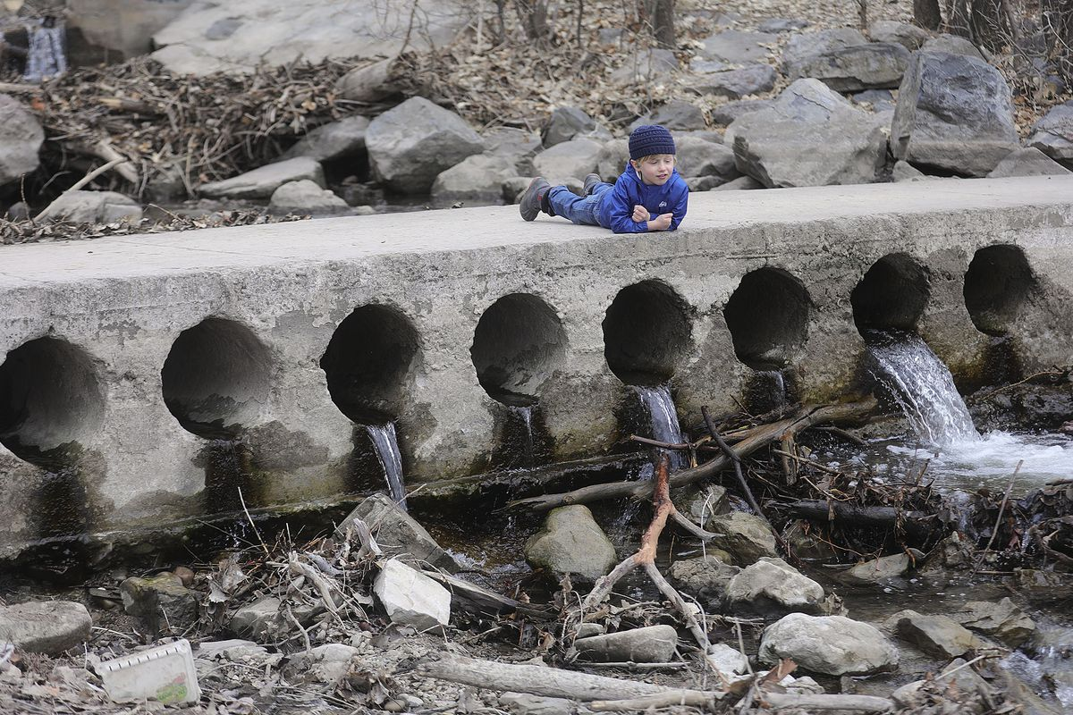 Henry Hovey, 4, watches as water from Parleys Creek as it flows into the pond at Sugar House Park in Salt Lake City on Tuesday, Feb. 9, 2021. With a shallow snowpack, water runoff is expected to be less than normal this year.