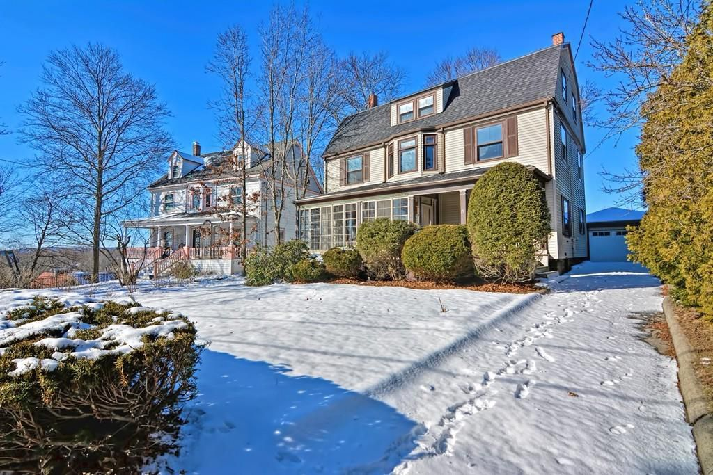 The back of a three-story, rectangular house as seen from a snow-covered yard.