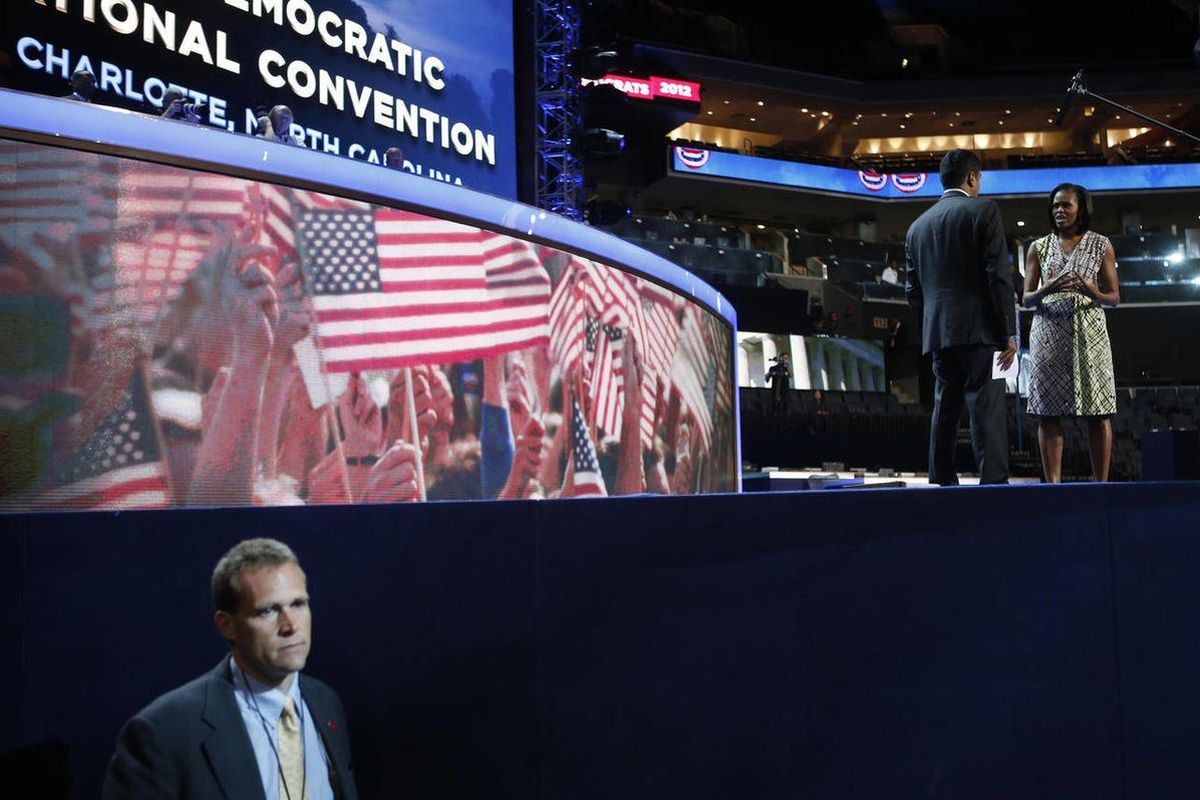 First Lady Michelle Obama, right, appears on the stage with actor Kal Penn for filming a campaign video, as a Secret Service agent watches the floor at the Democratic National Convention inside Time Warner Cable Arena in Charlotte, N.C., on Monday, Sept.