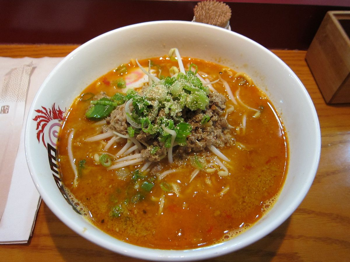 A reddish bowl of ramen with an opaque broth with spiraling fish cake and sprouts visible in addition to noodles.
