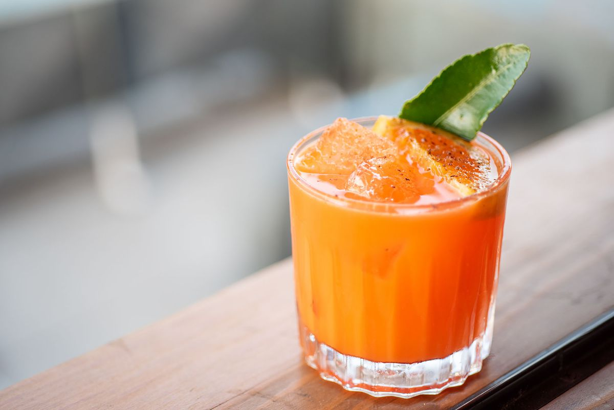 Bright orange cocktail with an orange garnish and ice cubes with a bright background.