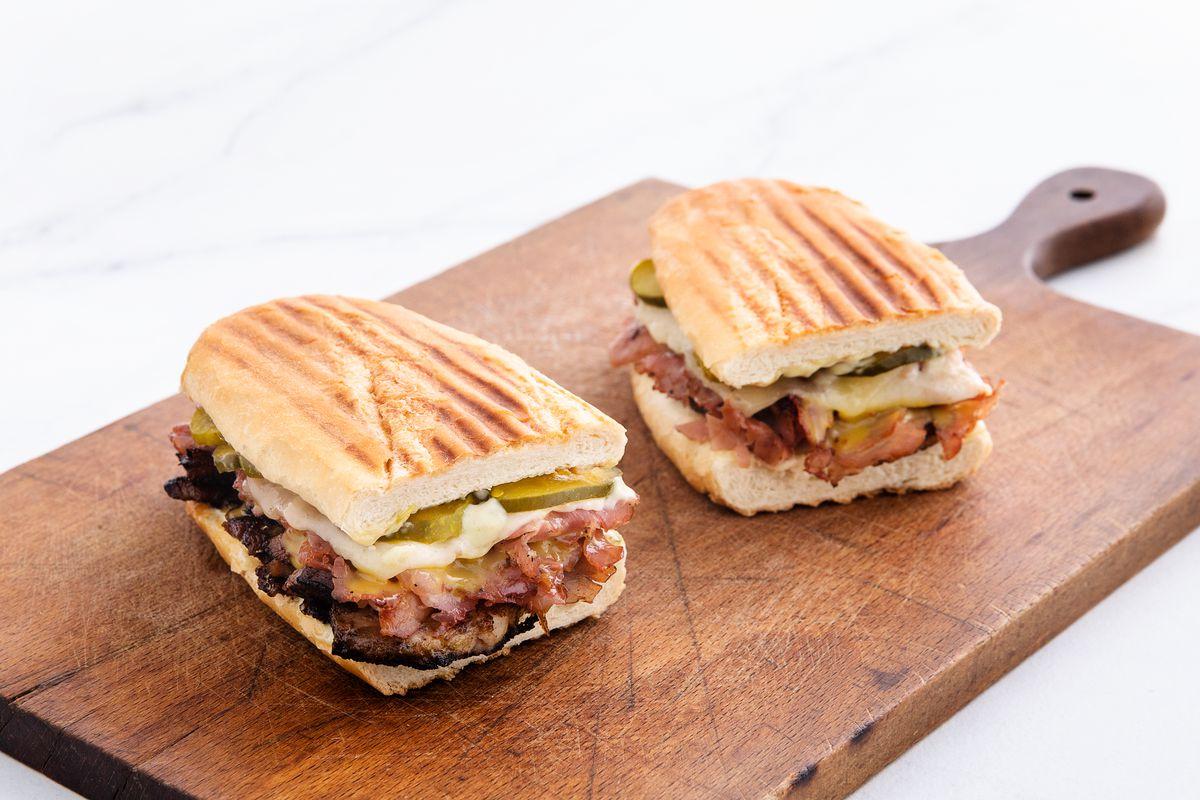 A pressed Cuban sandwich on a wood board
