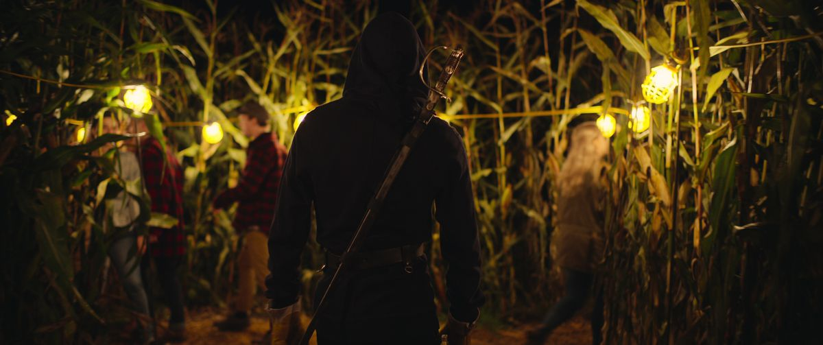 A hooded figure with a sword across their back stands in a cornfield, back to the camera, as other out-of-focus people enter the corn in There's Someone Inside Your House