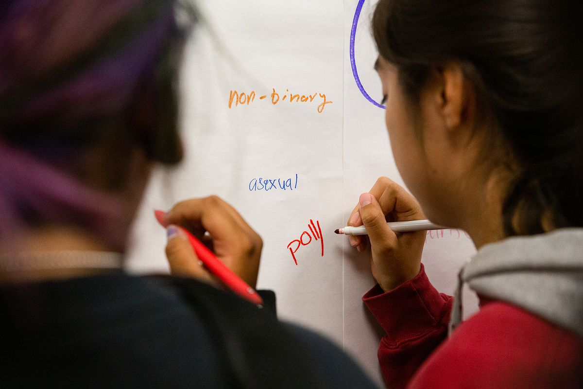 "Students write the words ""non-binary,"" ""asexual,"" and ""poly"" on paper posted on a wall."