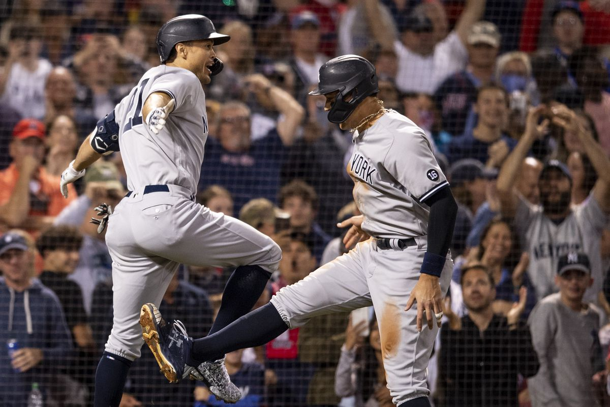 Giancarlo Stanton of the New York Yankees reacts with Aaron Judge after hitting a two run home run during the eighth inning of a game against the Boston Red Sox on September 26, 2021 at Fenway Park in Boston, Massachusetts.