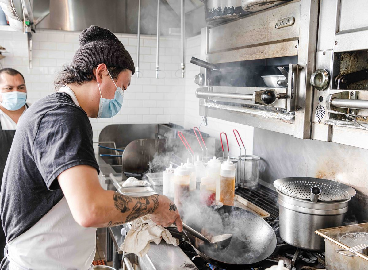 Chef Eric Ehler cooking a dish in the wok, his mouth covered by a face mask