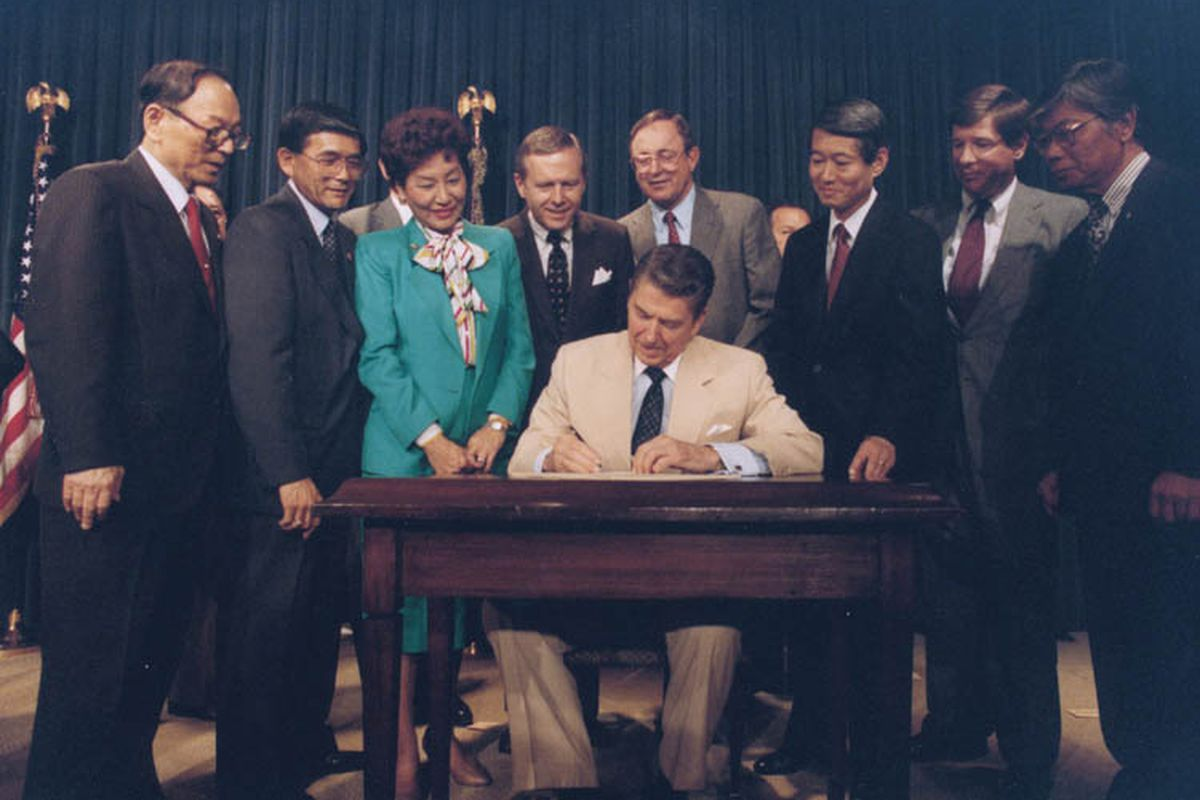 Ronald Reagan signs the Civil Liberties Act of 1988, establishing reparations for victims of Japanese internment, into law.