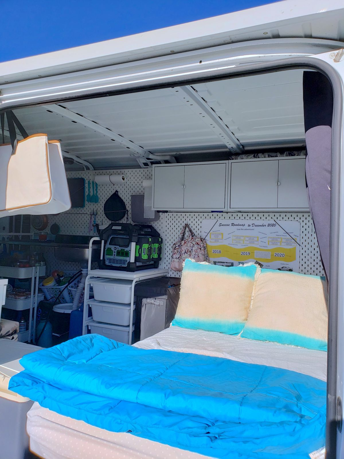 A bed in a white camper van features blue and white linens and a side door open.