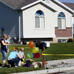 Annie Durrwachter, left, and her mother, Teresa Peterson, leave flowers at the crime scene in West Point on Thursday, May 23, 2013. Two young brothers were found dead in their West Point home late Wednesday. Their 15-year-old brother was booked into the Farmington Bay Youth Detention Center Thursday in connection with the deaths.