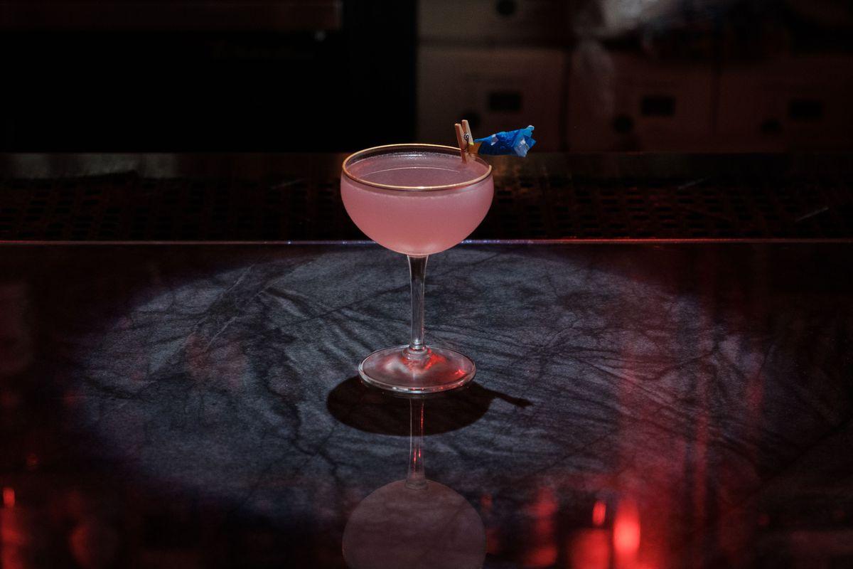 a pink cocktails served in a dark bar