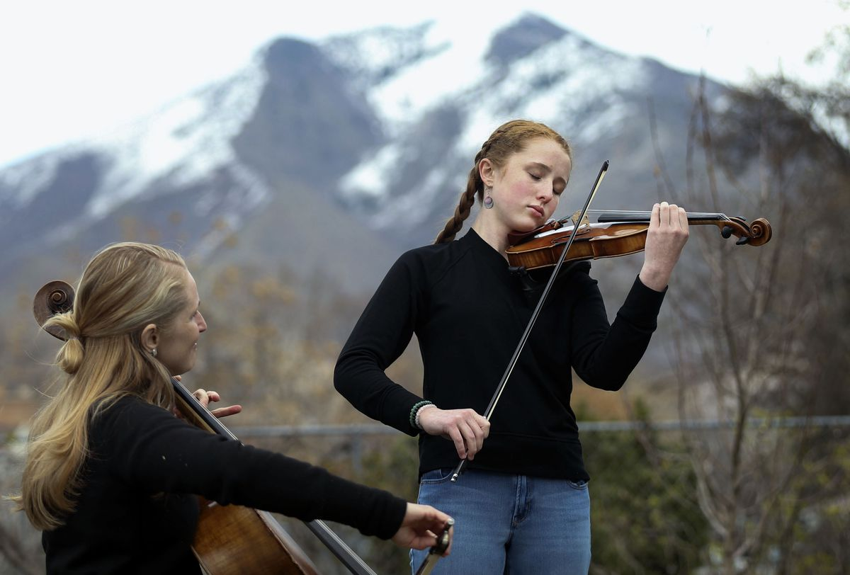 """Vivian Stewart, 13, and her mother, Kelly McConkie Stewart, play """"Consider the Lilies"""" for Helen Gygi in Salt Lake City on Wednesday, April 1, 2020. The mother/daughter duo have been performing concerts on the front yards of their neighbors and friends."""