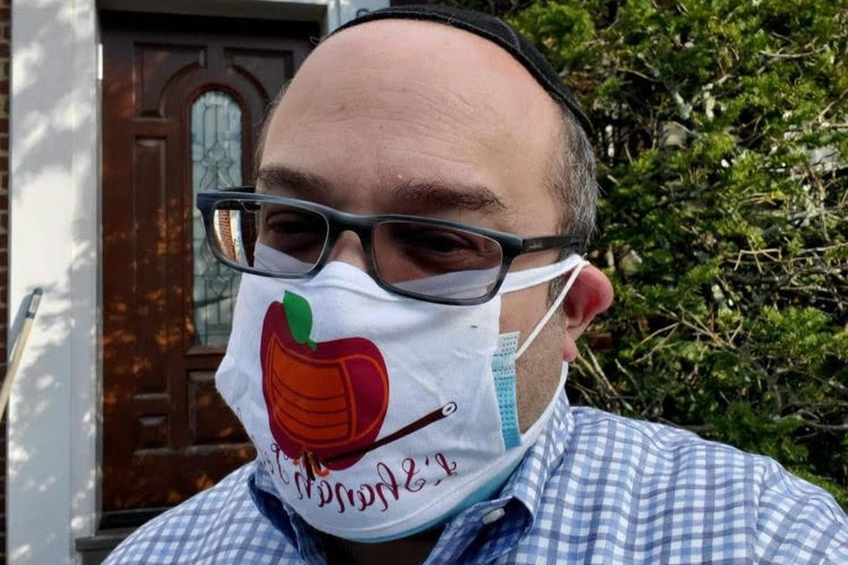 Rabbi Robert Blustein goes up and down the aisles of Ocean Parkway Jewish Center in Brooklyn making sure everyone has a mask and is wearing it properly, Oct. 5, 2020.