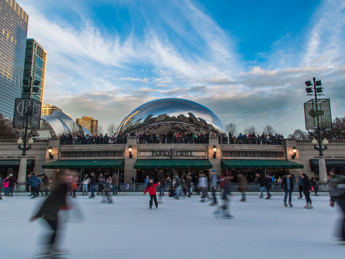 A group of people blurred by a long shutter speed skate on an ice rink with tall buildings in the background.