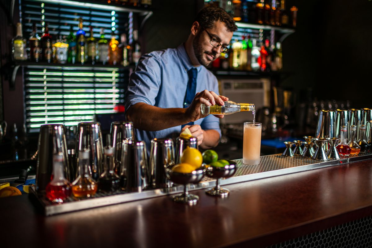 """Bartender Dylan Zehr making a """"Bitter Lemon"""" (gin, lemon, tonic, angostura) behind a bar constructed of PaperStone, an exceptionally dense material made from recycled paper."""