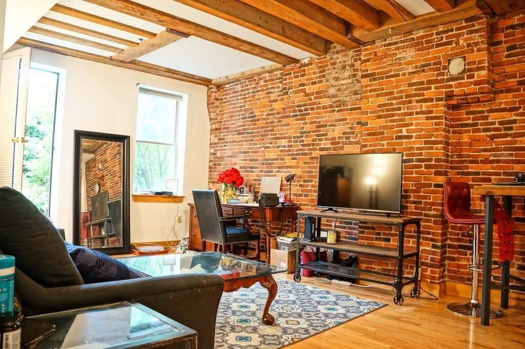 A living room with a high ceiling, beams on that ceiling, and a large exposed brick wall.