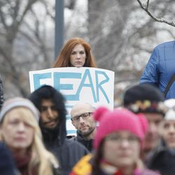 """Alisa Evans holds a two-sided sign reading """"Love more, fear less,: at the protest held by Utah Against Police Brutality outside the Salt Lake City Public Safety Building in Salt Lake City Saturday, Jan. 10, 2015."""