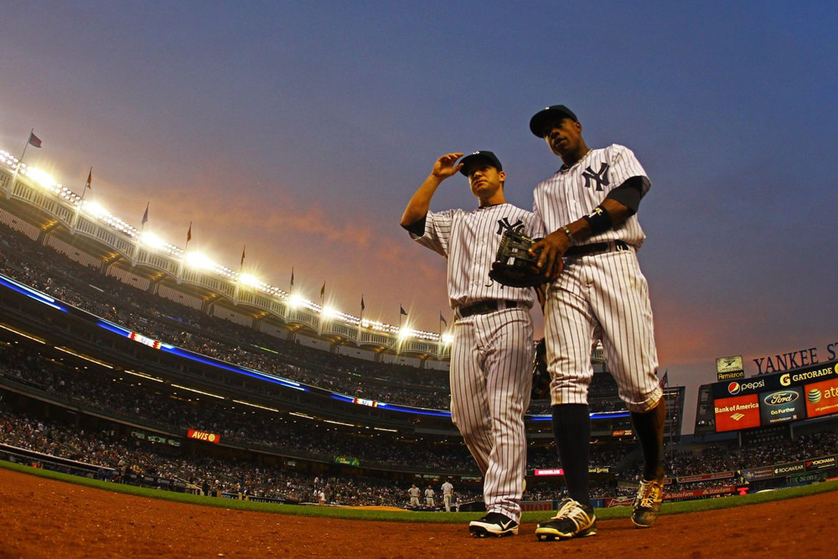 Jayson Nix and Curtis Granderson walk back to the dugout at Yankee Stadium.  (Photo by Al Bello/Getty Images)