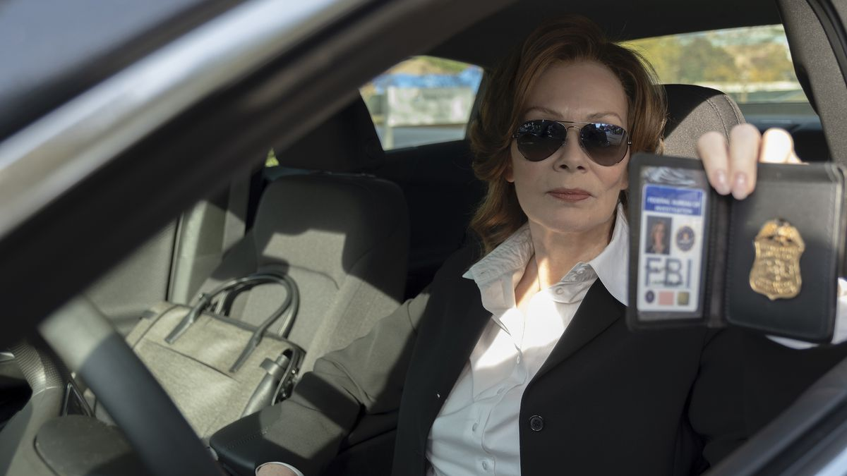 laurie (jean smart) rides up to the graveyard in shades and flashes her FBI badge